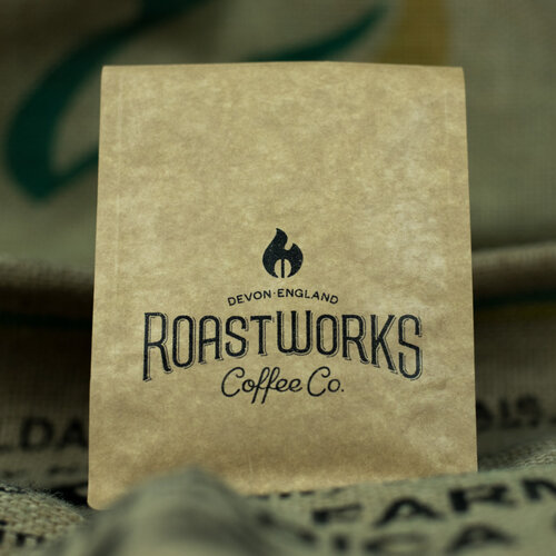 A roaster filling brown kraft paper bags with roasted coffee beans.