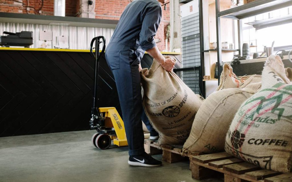 man dragging bag of coffee beans in roastery